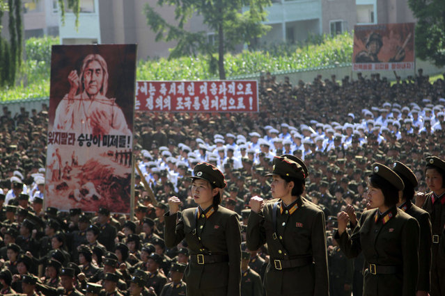 "Korean People's Army (KPA) officers and soldiers vow to smash the ""U.S. imperialists"" as they gather for a meeting to mark the 64th anniversary of the start of the Korean War, Wednesday, June 25, 2014, in South Hwanghae Province, North Korea. The writing on the sign in foreground left reads ""Don't forget the wolfish American imperialists!"" (Photo by Jon Chol Jin/AP Photo)"