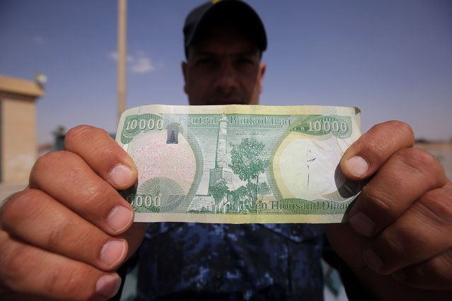 """An Iraqi policeman displays a 10,000-Iraqi dinar banknote bearing an image of Mosul's iconic leaning minaret, known as the """"Hadba"""" (Hunchback), on June 22, 2017, in Mosul. (Photo by Ahmad al-Rubaye/AFP Photo)"""