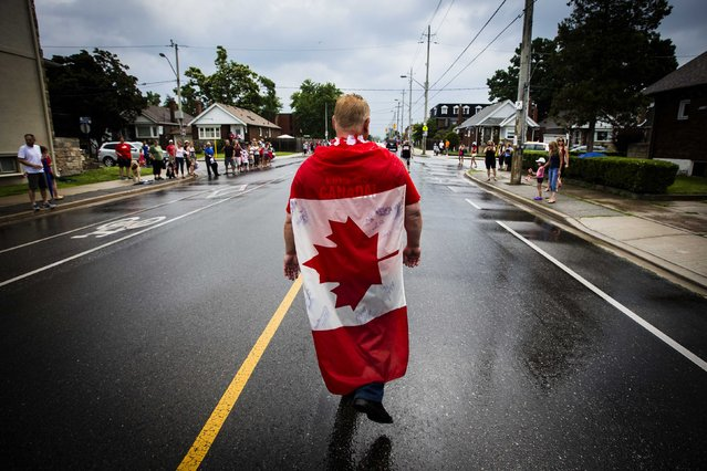 Doug Ford, brother and campaign manager of Toronto Mayor Rob Ford, walks with the Canadian flag draped on his back as he takes part in the East York Canada Day Parade in Toronto July 1, 2014. (Photo by Mark Blinch/Reuters)
