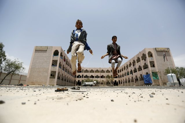 Boys skip at a school in Yemen's capital Sanaa sheltering people after the conflict forced them to flee their areas from the Houthi-controlled northern province of Saada August 4, 2015. A Saudi-led Arab alliance launched a military campaign on March 26 to end Houthi control over much of Yemen and to return President Abd-Rabbu Mansour Hadi from exile. (Photo by Khaled Abdullah/Reuters)