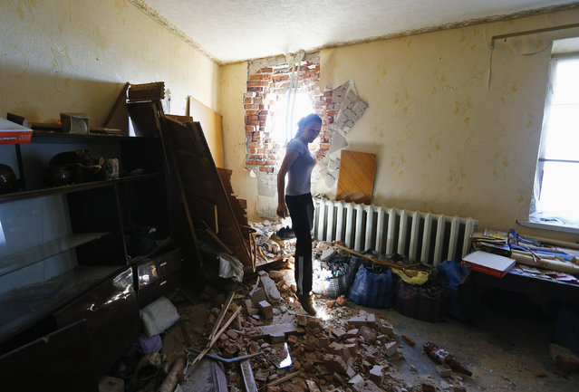 Local resident Tatyana Markova walks inside a house damaged by shelling in the Ukrainian eastern city of Slaviansk July 1, 2014. (Photo by Shamil Zhumatov/Reuters)