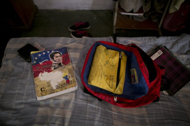 In this June 1, 2016 photo, Maria Arias' backpack and a book featuring Venezuela's independence hero Simon Bolivar sit on her bed before she leaves for school in Caracas, Venezuela. Arias' mother knows her children's grades have fallen this year, but isn't sure how much, because the school has not had supplies to print up report cards. (Photo by Ariana Cubillos/AP Photo)
