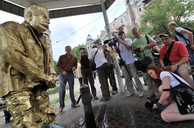 "People look at the ""Pissing Stalin Golden Monument"" created by activists of Ukrainian nationalist party Svoboda in Kiev on May 7, 2012 as art-provocation before V-day celebration"