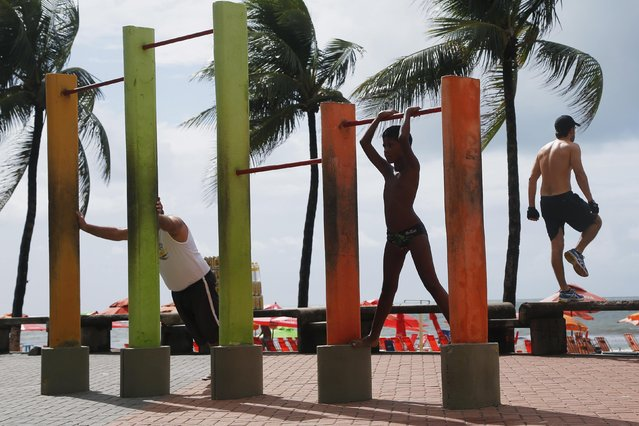 """A boy stretches on a pull-up bar as men exercise around him along the beach in Recife, on June 24, 2014. In a project called """"On The Sidelines"""" Reuters photographers share pictures showing their own quirky and creative view of the 2014 World Cup in Brazil. (Photo by Brian Snyder/Reuters)"""