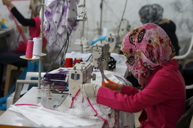 Women sew while working in a garment factory in Idlib city, Syria July 26, 2015. (Photo by Ammar Abdullah/Reuters)