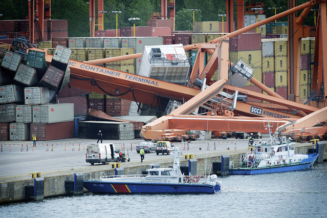 People look on after the gantry of the Baltic Container Terminal fell down onto shipping containers at the waterfront in Gdynia, Poland. Three people were injured in the accident