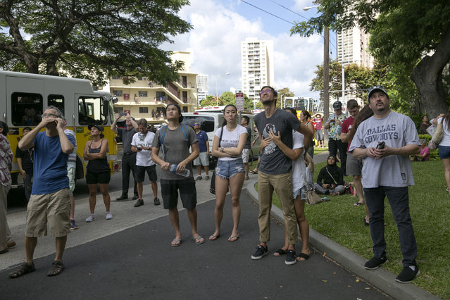 Crowds gather to watch a fire burn at the Marco Polo apartment complex, Friday, July 14, 2017, in Honolulu. (Photo by Marco Garcia/AP Photo)