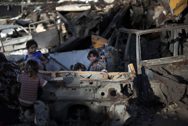 In this Monday, June 20, 2016 photo, Palestinian children play among discarded vehicles in el-Zohor slum, on the outskirts of Khan Younis refugee camp, southern Gaza Strip. (Photo by Khalil Hamra/AP Photo)