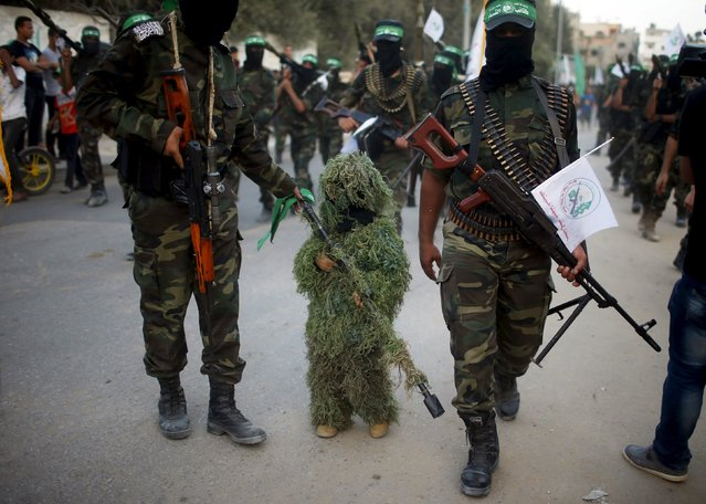 A masked Palestinian boy takes part with Hamas militates in an anti-Israel military parade in Beit Hanoun town in the northern Gaza Strip August 11, 2015. (Photo by Suhaib Salem/Reuters)