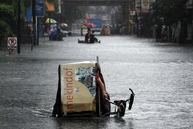 A resident riding a tricycle negotiates floodwaters after a sudden heavy downpour inundated streets in the financial district of Manila on August 12, 2015, stranding thousands of commuters and office workers. Hundreds of people are killed in natural disasters each year in the Philippines, which is battered by an average of 20 typhoons and tropical storms annually. (Photo by Ted Aljibe/AFP Photo)