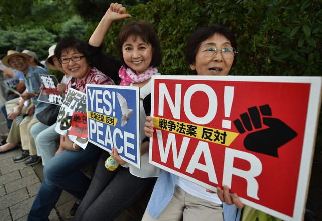 People hold placards during an anti-government rally near the Prime Minister's official residence in Tokyo on August 14, 2015. Abe expressed deep remorse over World War II and said previous national apologies were unshakeable, but emphasised future generations should not have to keep saying sorry. (Photo by Kazuhiro Nogi/AFP Photo)