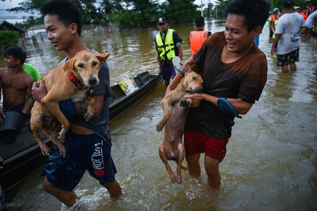 Residents carry their dogs to a boat as floodwaters submerged areas of Ye township in Mon State on August 11, 2019. Myanmar troops deployed to flood-hit parts of the country on August 11 to help with relief efforts after rising waters left thousands stranded and the death toll from a landslide jumped to 51. (Photo by Ye Aung Thu/AFP Photo)
