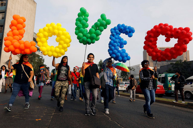 People walk with balloons during a gay pride parade in downtown Lima, Peru on July 2, 2016. (Photo by Guadalupe Pardo/Reuters)