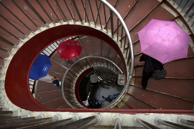 People holding umbrellas climb an outdoor staircase on a rainy day in Beijing, Thursday, June 22, 2017. Although Beijing is in a semi-dry climate, it receives much of its annual precipitation during the summer months. (Photo by Mark Schiefelbein/AP Photo)