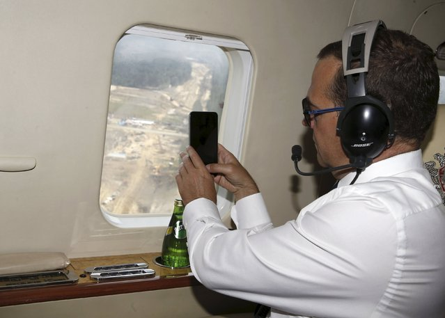 Russian Prime Minister Dmitry Medvedev takes pictures with his phone from aboard a helicopter while in flight from the city of Blagoveshchensk to the Vostochny cosmodrome near the village of Uglegorsk in Amur region, Russia, August 21, 2015. (Photo by Dmitry Astakhov/Reuters/RIA Novosti)