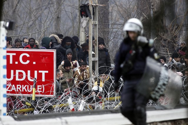 A Greek riot policeman patrols the border gate in Kastanies village as migrants trying to enter Greece from the Pazarkule border gate, Edirne, Turkey, gather at the Greek-Turkish border Saturday, February 29, 2020. (Photo by Giannis Papanikos/AP Photo)