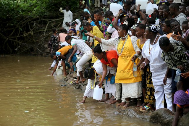 Worshippers of river goddess Osun pray at the river bank during the Osun-Osogbo annual festival in Osogbo,  Nigeria, in this August 21, 2015 picture. (Photo by Akintunde Akinleye/Reuters)