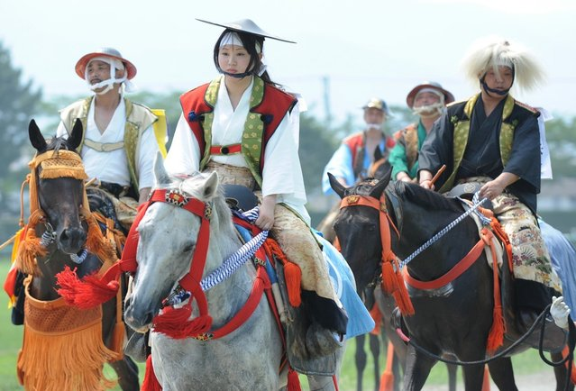 A young woman (C) clad in samurai costume leads other local poeple as she rides her horse during a parade at the annual Soma Nomaoi festival in Minamisoma, Fukushima Prefecture, on July 28, 2012.  The traditional full-scale festival kicked off for the first time after the accident of the Fukushima Dai-ichi Nuclear Power Plant following the massive earthquake and the tsunami on March 11, 2011. (Photo by Toru Yamanaka/AFP Photo)