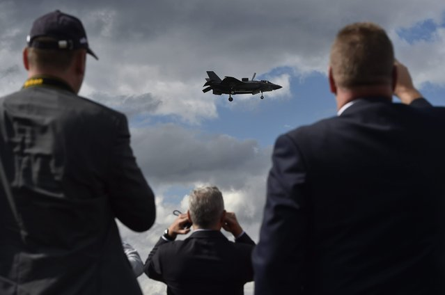 Plane enthusiasts watch the F35 perform during a flying display at the Farnborough International Airshow in Farnborough, Britain, 12 July 2016. (Photo by Hannah Mckay/EPA)