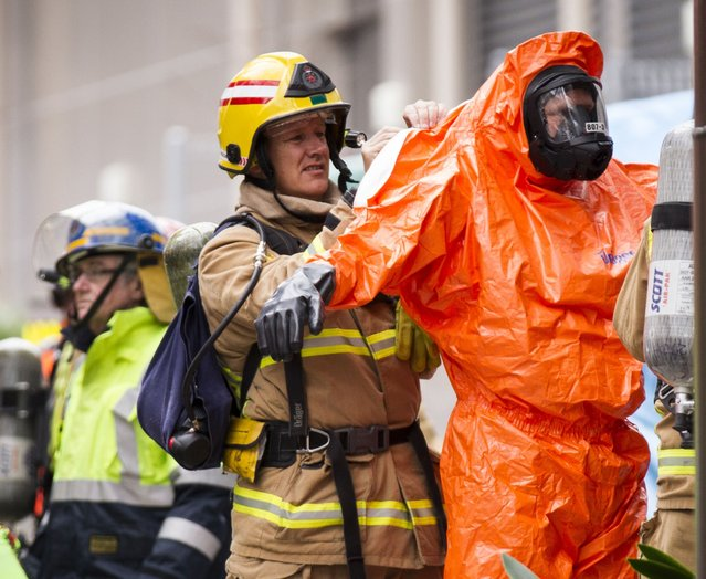 Emergency services workers prepare for operation at the Hotel Grand Chancellor in Auckland, New Zealand Tuesday August 25, 2015. A 58-year-old man facing fraud charges died in his Auckland hotel room Tuesday and sparked wider alarm after authorities said they found a brew of toxic gas inside. (Photo by Dean Purcell/New Zealand Herald Via AP Photo)
