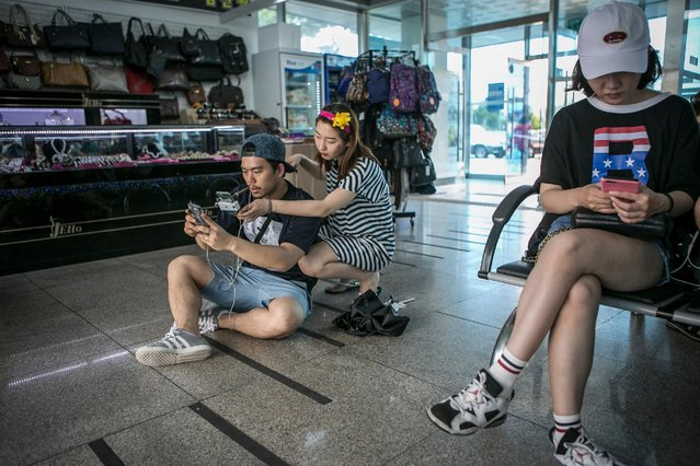 Lee Jeong-hwan (L) and Barbie Lim (second from left), broadcasting jockeys for Pokemon Go Korea Facebook page, broadcast live as Lee plays the game at the Express Bus Terminal on July 15, 2016 in Sokcho, South Korea. (Photo by Jean Chung/Getty Images)