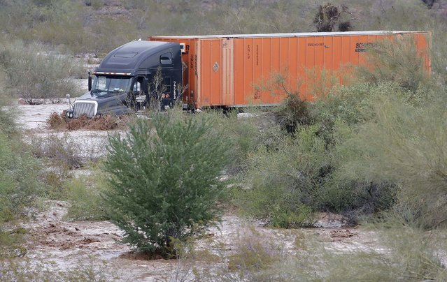 A tractor trailer drives through flash flood waters that overran Skunk Creek, Tuesday, August 19, 2014, in northwestern Phoenix. Flooding from heavy rain in the Phoenix area has forced authorities to close several major roads, including a portion of Interstate 17 about 25 miles north of the city. (Photo by Matt York/AP Photo)