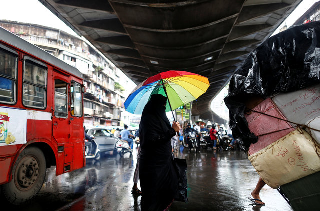 A woman carrying an umbrella crosses a street in Mumbai, India, July 18, 2016. (Photo by Danish Siddiqui/Reuters)