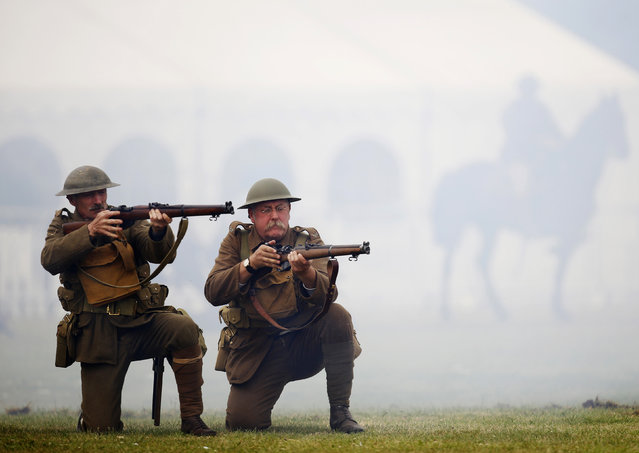 Freight train driver Chris Bingham (R), portraying a private, from the Queen's Own Royal West Kent Living History Group, and carpenter Richard Helad (L), portraying a Lance Corporal, participate in a mock battle illustrating the First World War at the Colchester Military Tournament in Colchester, eastern England July 6, 2014. (Photo by Luke MacGregor/Reuters)