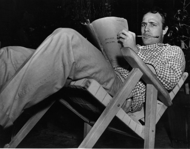 """Marlon Brando is seen relaxing at his Hollywood, Calif., home on August 3, 1954. Brando studies the script for next day's shooting of  """"Desiree"""", in which he plays Napoleon. (Photo by AP Photo)"""