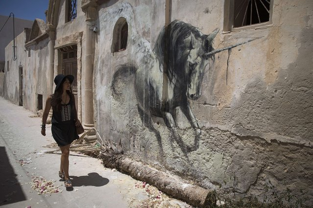 "A woman looks at a mural by South African artist FAITH 47 which decorates a wall in the village of Erriadh, on the Tunisian island of Djerba, on August 8, 2014, as part of the artistic project ""Djerbahood"". (Photo by Joel Saget/AFP Photo)"