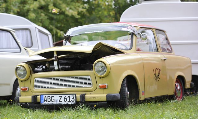 The engine cowling of a Trabant 601 car is held by a beer bottle as fans of the East German Trabant car gather for their 7th annual get-together on August 23, 2014 in Zwickau, Germany. Hundreds of Trabant enthusiasts arrived to spend the weekend admiring each others cars, trading stories and enjoying activities. The Trabant, dinky and small by modern standards, was the iconic car produced in former communist East Germany and today has a strong cult following. (Photo by Matthias Rietschel/Getty Images)