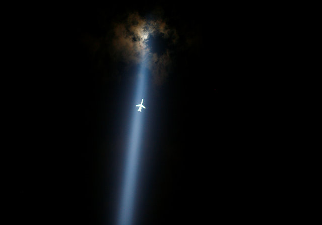 """A plane flies through the """"Tribute in Lights"""" marking the 10th anniversary of the 9/11 attacks in lower Manhattan, New York, U.S., September 10, 2011. (Photo by Eric Thayer/Reuters)"""