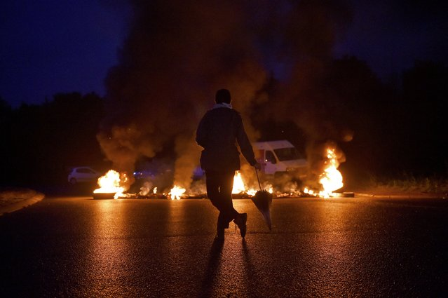 A protestor looks at a fire displayed on a traffic circle as union trade members block trucks on September 25, 2017 in Donges, western France, to protest against the government's labour law. (Photo by Loic Venance/AFP Photo)