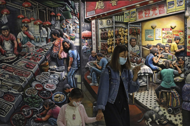 A woman and a girl wearing face masks to protect themselves from possibly contracting the coronavirus COVID-19 as they walk past a painting in Hong Kong, Saturday, April 25, 2020. (Photo by Kin Cheung/AP Photo)