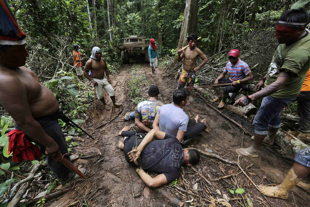 Ka'apor Indian warriors tie up loggers during a jungle expedition to search for and expel them from the Alto Turiacu Indian territory, near the Centro do Guilherme municipality in the northeast of Maranhao state in the Amazon basin, August 7, 2014. (Photo by Lunae Parracho/Reuters)