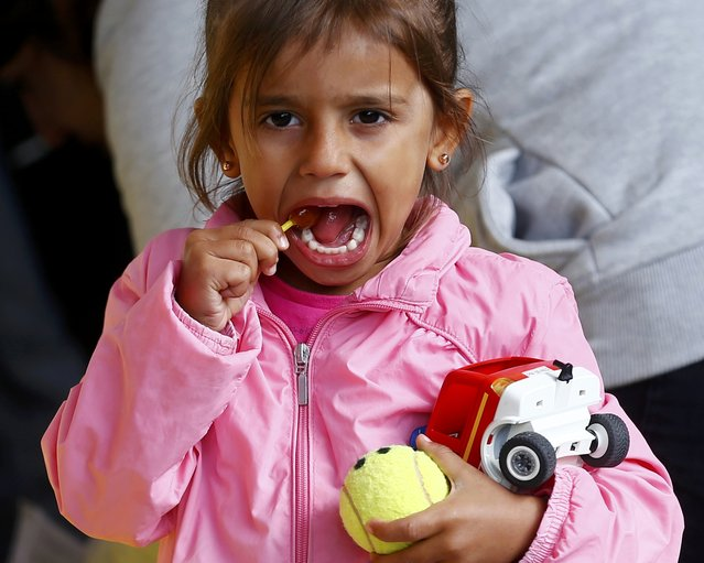 A young migrant girl enjoys a lollypop after arriving at a railway station in Vienna, Austria September 6, 2015. (Photo by Dominic Ebenbichler/Reuters)