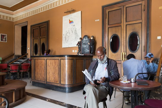 """""""In the old Roma cinema in Asmara, men drink macchiato and read the only national newspaper"""", explains Buret of this shot. """"Freedom of the press doesn't exist"""". (Photo by Stéphanie Buret/The Guardian)"""
