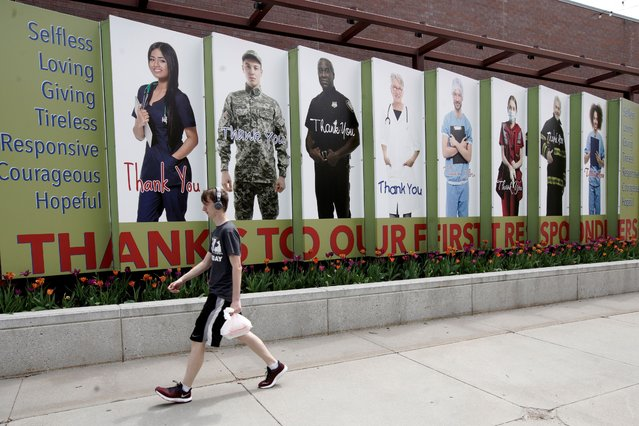 A person carries a bag in front of a mural expressing appreciation for first responders, in Omaha, Neb., Tuesday, April 28, 2020. Gov. Pete Ricketts defended his decision Monday to ease social-distancing restrictions in some parts of Nebraska, even though the number of confirmed coronavirus cases has surged in the last few days. (Photo by Nati Harnik/AP Photo)