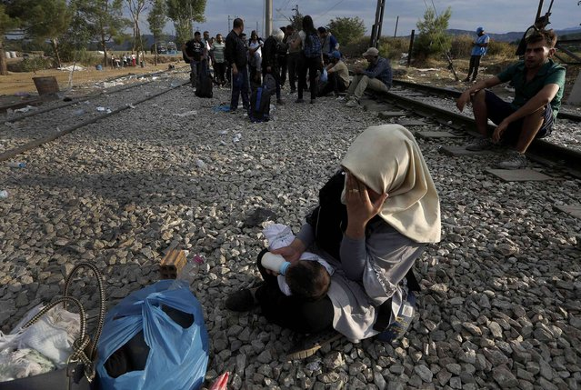 An Iraqi refugees feeds her baby as she wait to cross Greece's border with Macedonia, near the Greek village of Idomeni, September 7, 2015. (Photo by Yannis Behrakis/Reuters)