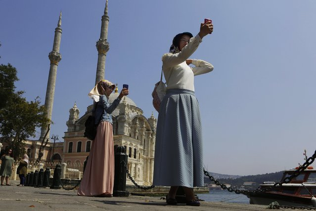Women take photos outside from the Ortakoy Mosque at the sea side of Istanbul, on Monday, August 1, 2016. Turkey slammed a German court decision that prevented President Recep Tayyip Erdogan from addressing a demonstration in Germany denouncing Turkey's failed July 15 coup, and summoned a German diplomat in protest. (Photo by Petros Karadjias/AP Photo)