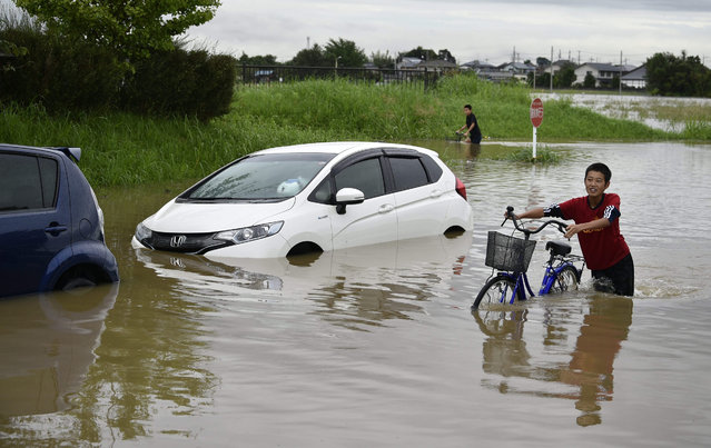 A young boy pushes a bicycle in a street flooded due to heavy rain generated by typhoon Etau in a residential area of Koshigaya, Saitama prefecture, north of Tokyo, Japan, 10 September 2015. According to local media reports, one person was feared dead and another missing and some 150,000 residents were ordered to evacuate their homes as flooding and mudslides hit eastern Japan. (Photo by Franck Robichon/EPA)