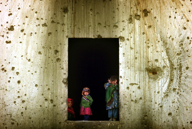 Afghan refugee children look from the window of their shelter in the former Soviet embassy, a huge compound amid the destruction of west Kabul, November 27, 2001. (Photo by Damir Sagolj/Reuters)