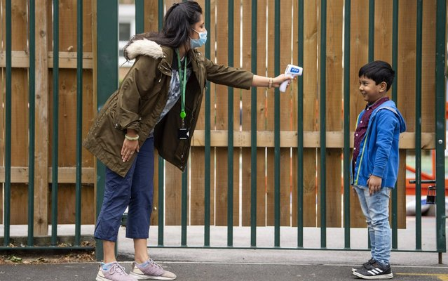 A child has his temperature checked by a teacher before entering Earlham Primary School, which is part of the Eko Trust on June 10, 2020 in London, England. As part of Covid-19 lockdown measures, Earlham Primary School is teaching smaller 'bubbles' of students, to help maintain social distancing measures. School staff have put into place many safety measures such as corridor signage for a one way system, regular supervised handwashing, temperature checks on arrival and enhanced cleaning regimes to keep pupils and staff as safe as possible. Bubbles of pupils are limited to six and each have their own well-ventilated space. The Government have announced it is set to drop plans for all English primary pupils to return to school before the end of the summer. (Photo by Justin Setterfield/Getty Images)