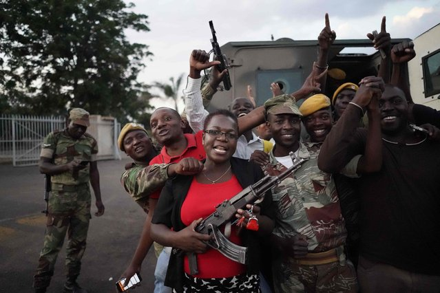 People and soldiers celebrate after the resignation of Zimbabwe' s president on November 21, 2017 in Harare. Car horns blared and cheering crowds raced through the streets of the Zimbabwean capital Harare as news spread that President Robert Mugabe, 93, had resigned after 37 years in power. (Photo by Marco Longari/AFP Photo)