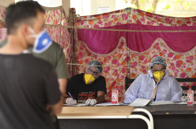 An Indian doctor interacts with a man as another waits for his turn at COVID-19 screening facility inside a government run hospital in Jammu, Saturday, June 27, 2020. India is the fourth hardest-hit country by the pandemic in the world after the U.S., Russia and Brazil. (Photo by Channi Anand/AP Photo)