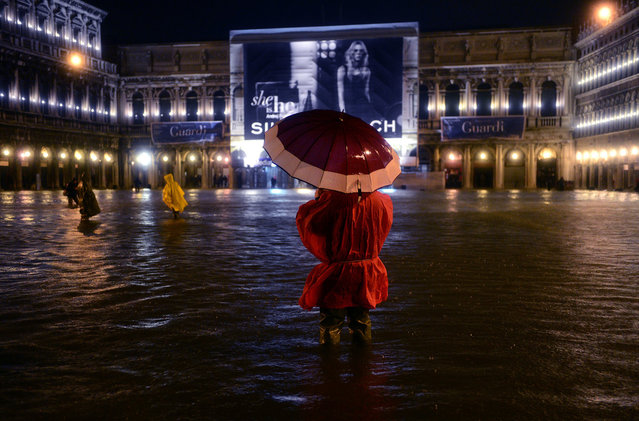 """A man walks on the flooded Saint Mark's square during an """"acqua alta"""" (""""high waters"""") flooding on October 31, 2012 in Venice. The """"acqua alta"""" reached 140 centimeters at midnight. (Photo by Oliver Morin/AFP Photo)"""