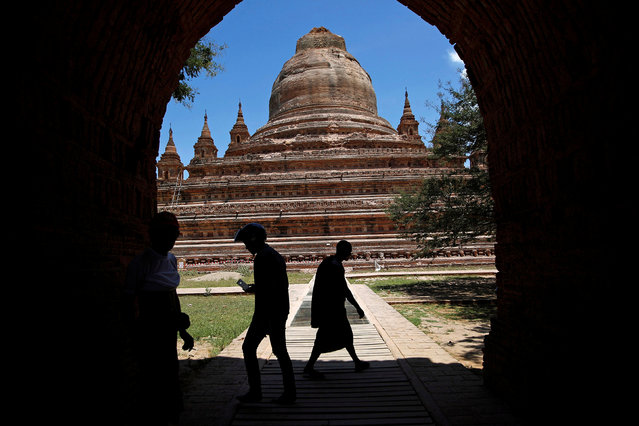 People walk as the top of a collapsed pagoda is seen in the background after an earthquake in Bagan, Myanmar August 25, 2016. (Photo by Soe Zeya Tun/Reuters)