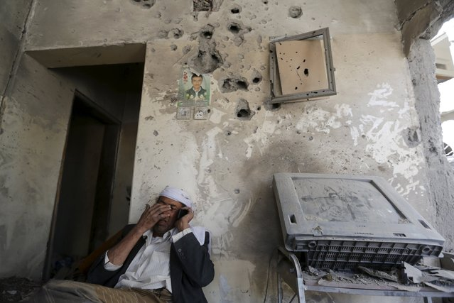 Mahyoub al-Hemiari talks on the phone inside his house which is detroyed by a Saudi-led air strike in Yemen's capital Sanaa,September 17, 2015. At least nine Yemeni civilians were killed in air strikes by Saudi-led warplanes that targeted the home of a leader in the dominant Houthi movement in the capital Sanaa, medical sources said on Thursday. (Photo by Khaled Abdullah/Reuters)