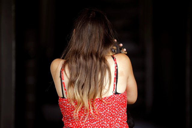 A woman carries her dog amid the spread of the coronavirus disease (COVID-19), in Ashkelon, Israel on July 6, 2020. (Photo by Amir Cohen/Reuters)