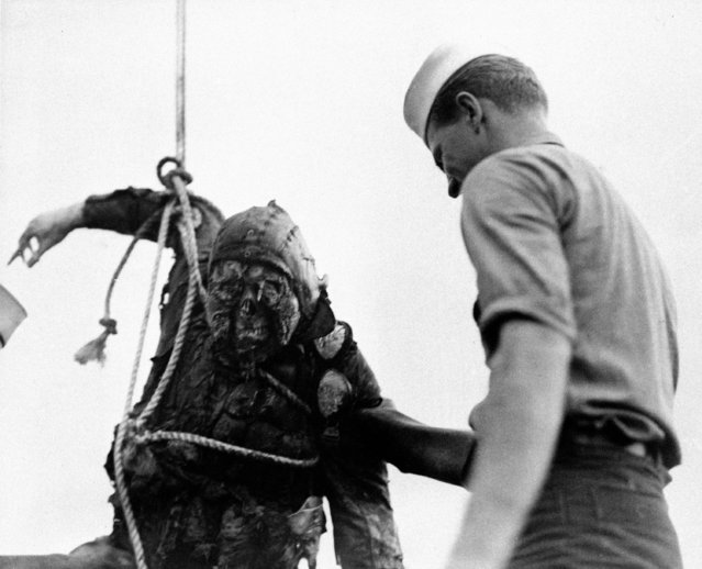 An American Seaman looks at the charred corpse of a Japanese flier brought up from the bottom of Pearl Harbor, where he crashed with his burning plane during the attack. (Photo by Associated Press)